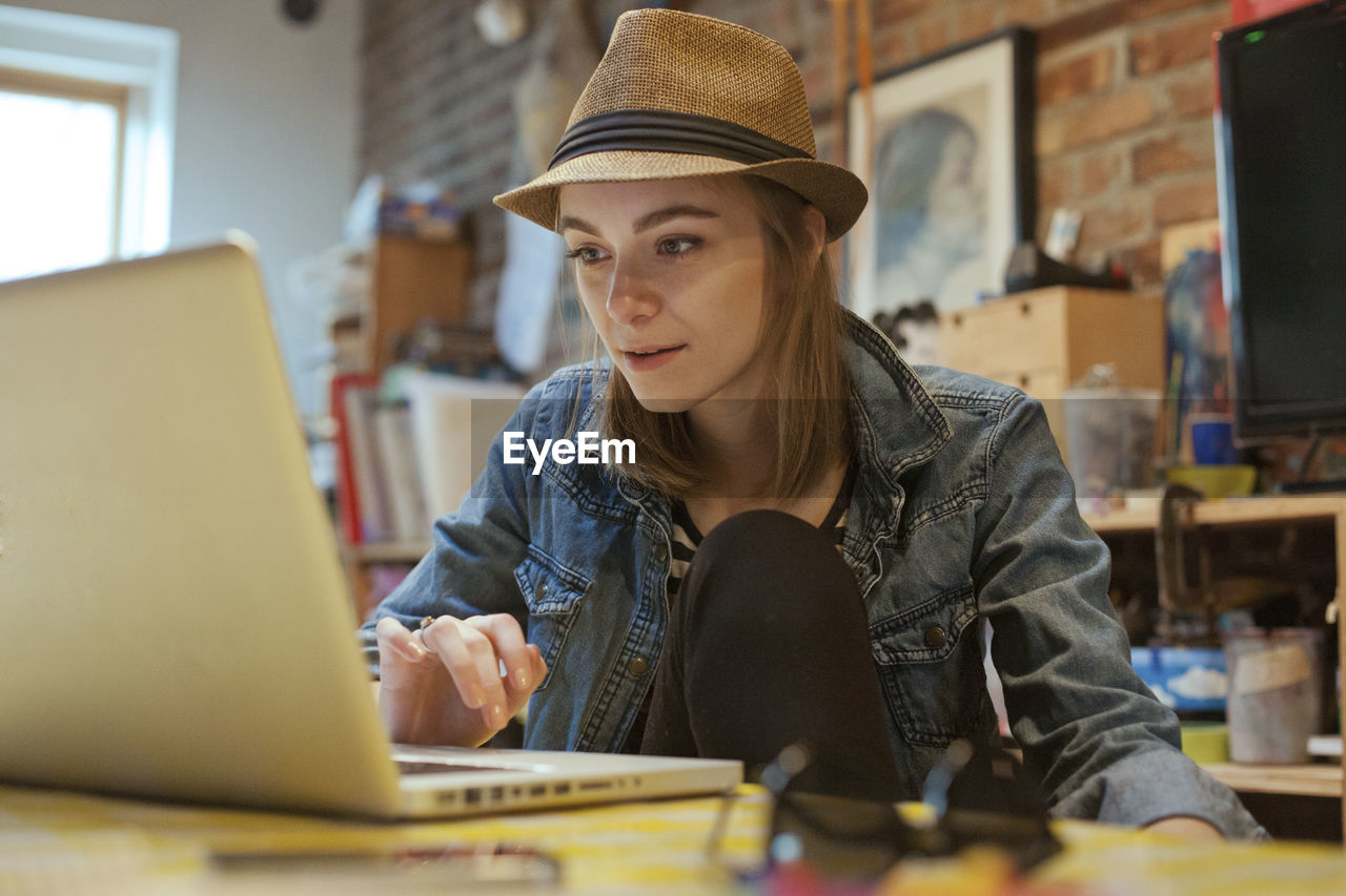 wireless technology, one person, technology, laptop, computer, real people, sitting, hat, indoors, using laptop, table, communication, working, young adult, connection, clothing, waist up, portrait, casual clothing, surfing the net, hairstyle