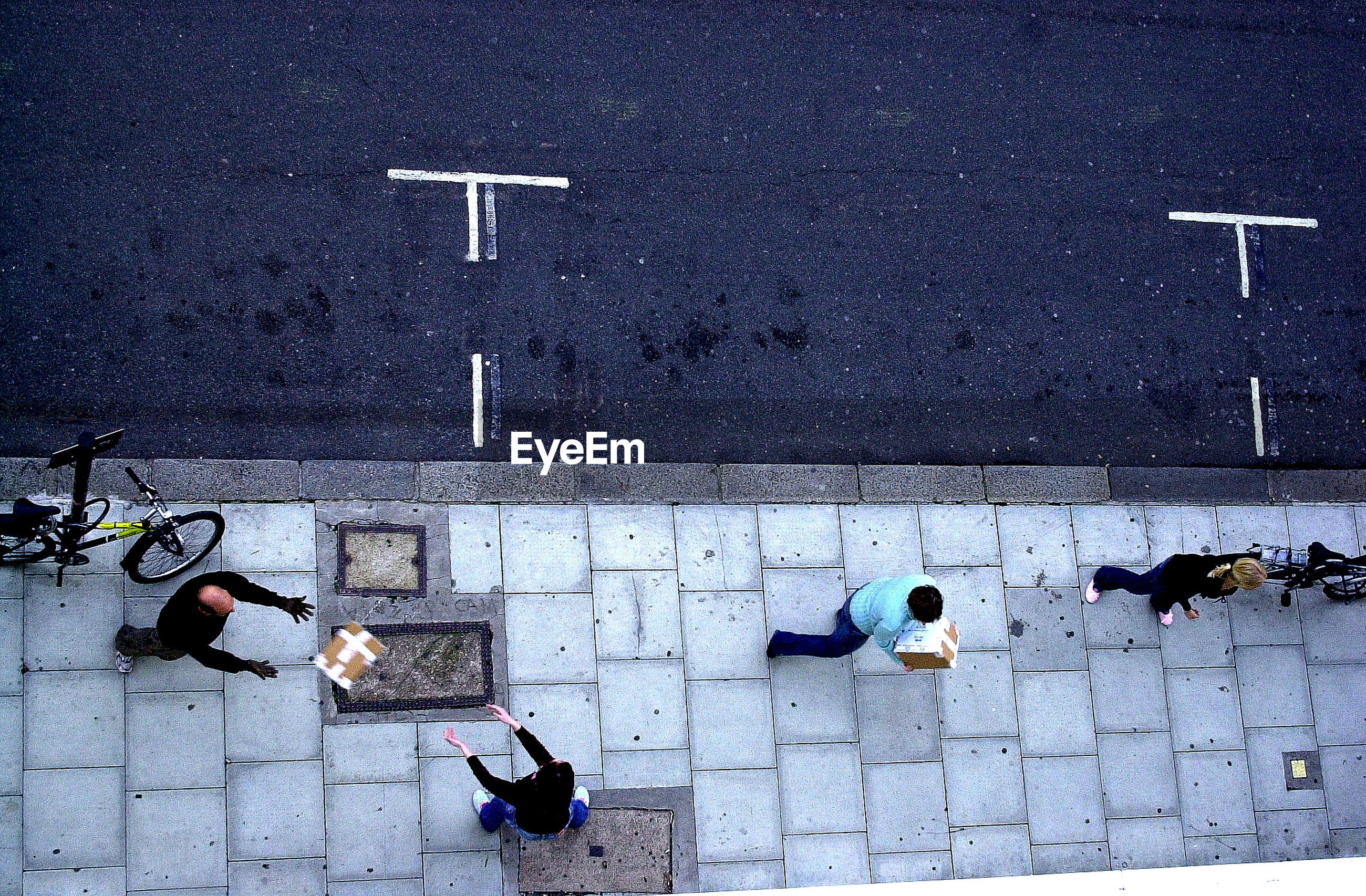 Directly above shot of people with cardboard boxes while standing on sidewalk