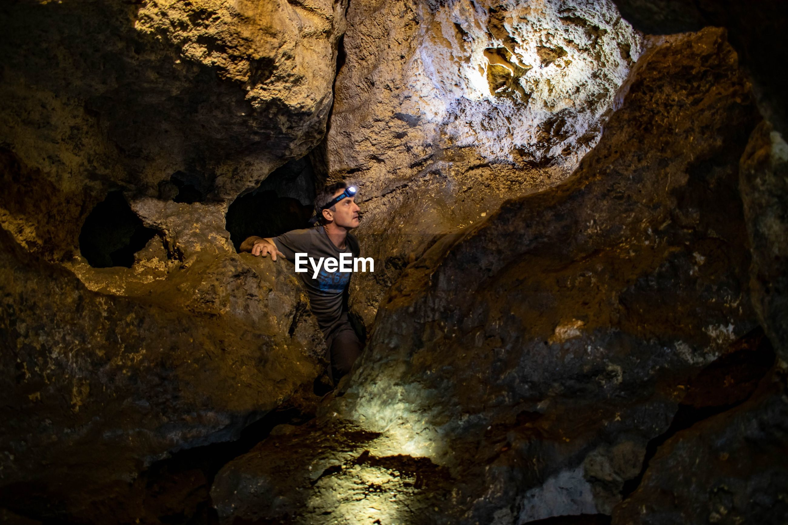 Mature man looking at rocks in cave