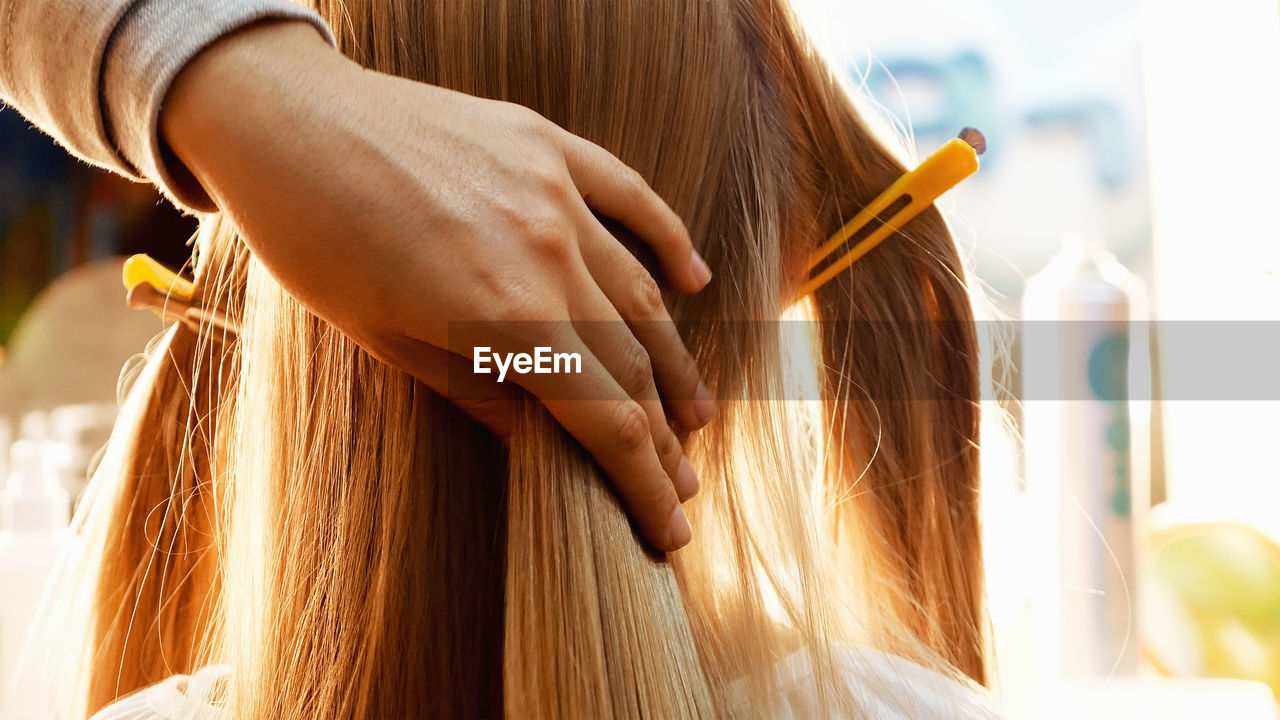 Cropped hands of female hairstylist styling girl hair