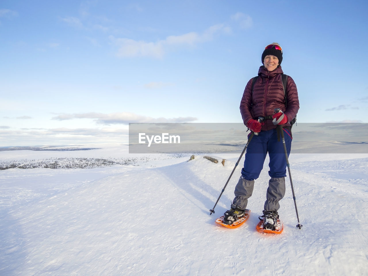 Portrait Of Smiling Mid Adult Woman Skiing On Snowcapped Mountain
