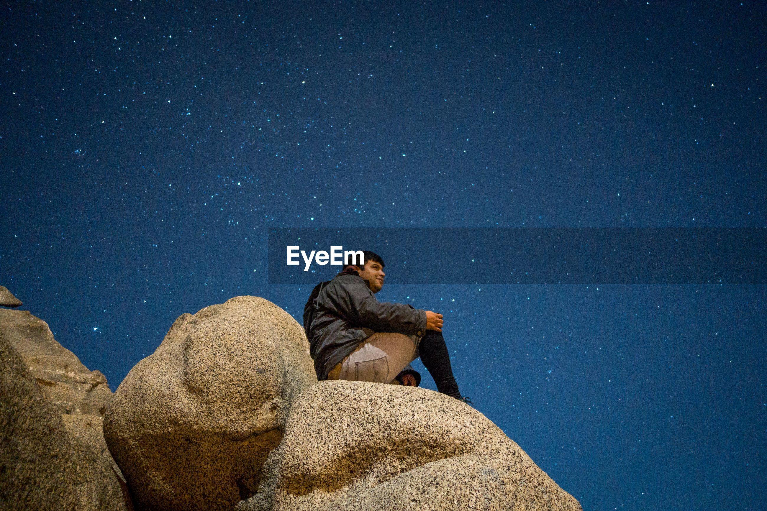Man on rock formation at night