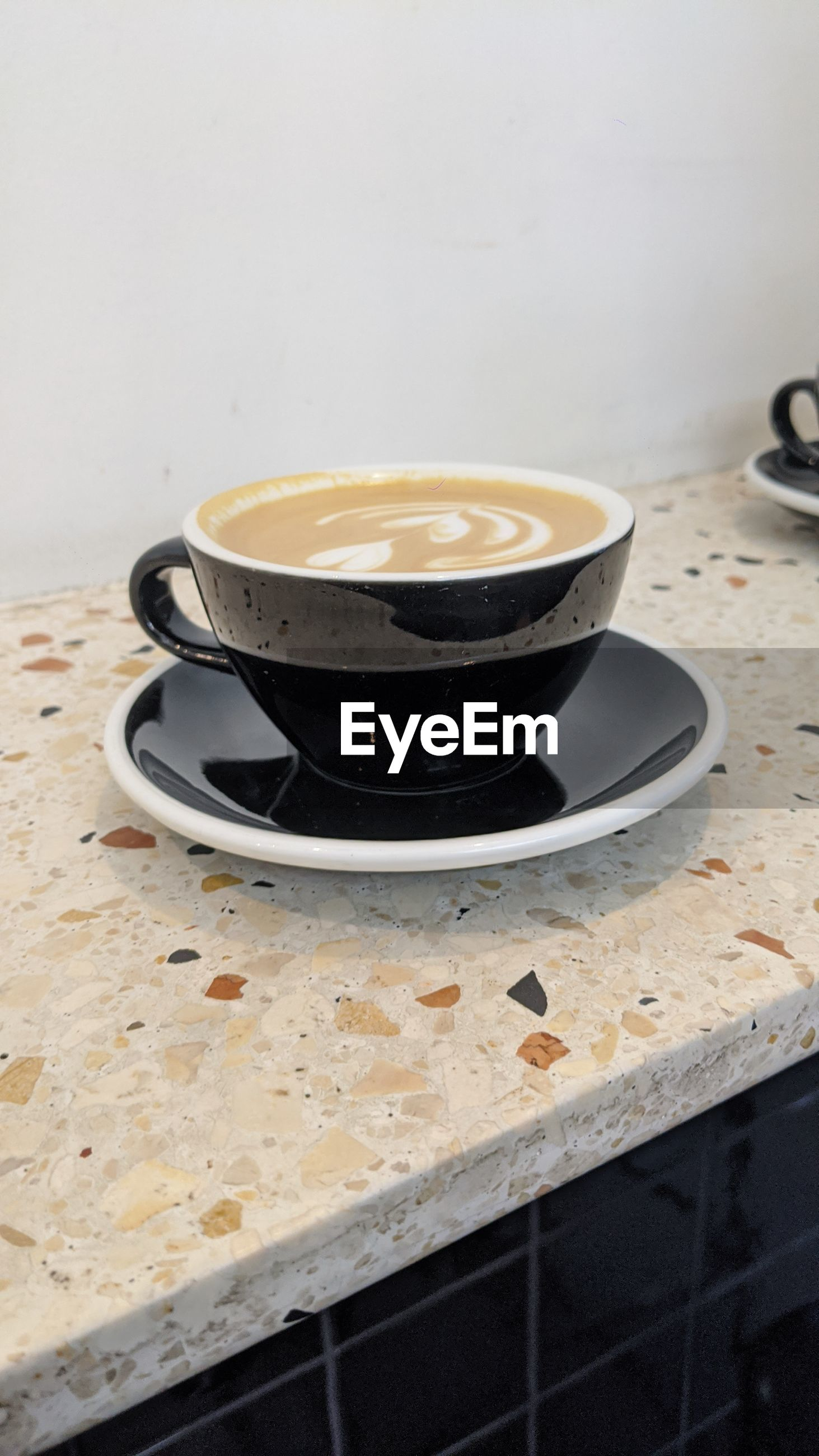 HIGH ANGLE VIEW OF COFFEE CUP ON TABLE AGAINST WALL