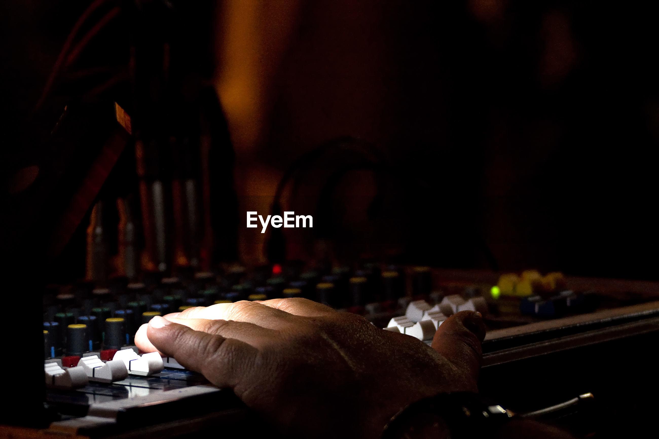Cropped hand of dj using sound mixer in darkroom