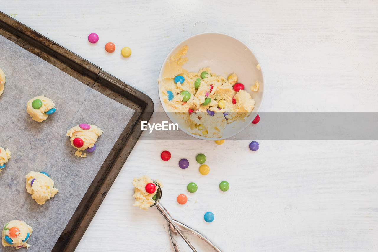 multi colored, food, food and drink, high angle view, table, freshness, wood - material, sweet food, still life, indoors, no people, directly above, sweet, candy, indulgence, unhealthy eating, bowl, temptation, ready-to-eat, kitchen utensil