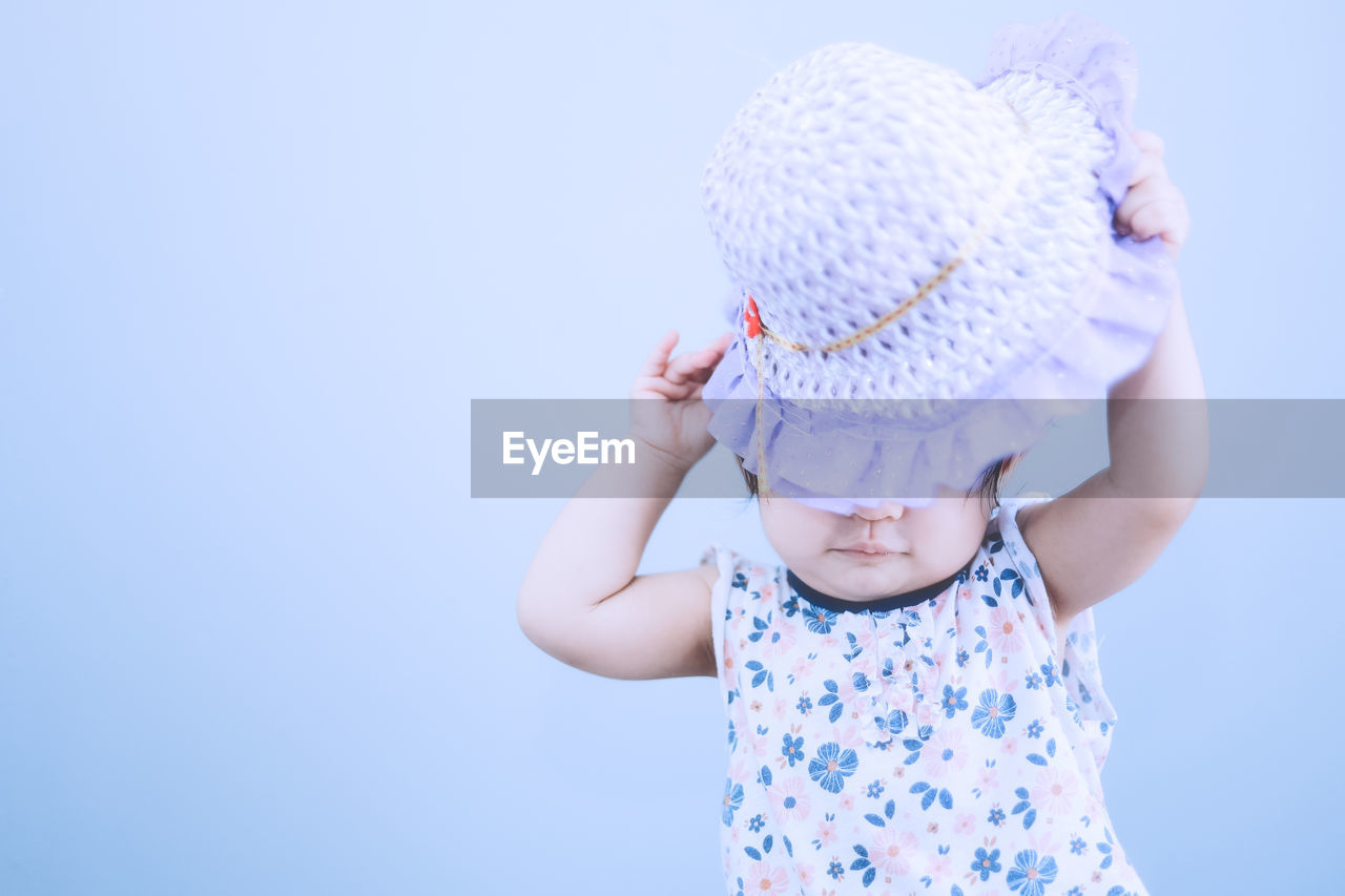 childhood, child, innocence, cute, baby, young, real people, hat, babyhood, front view, one person, copy space, casual clothing, clothing, toddler, leisure activity, blue, studio shot, human arm, arms raised