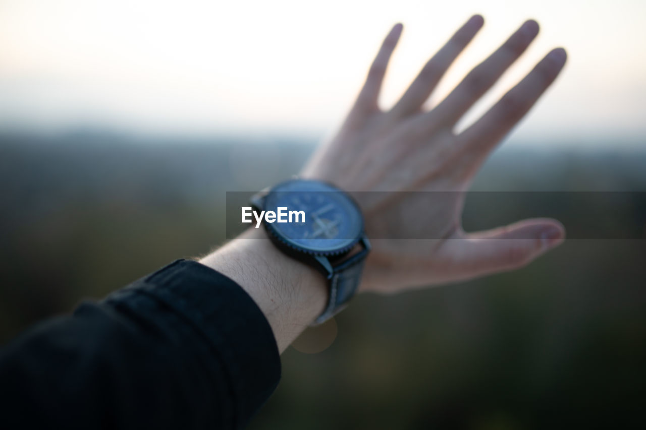 Cropped hand of man wearing watch gesturing outdoors