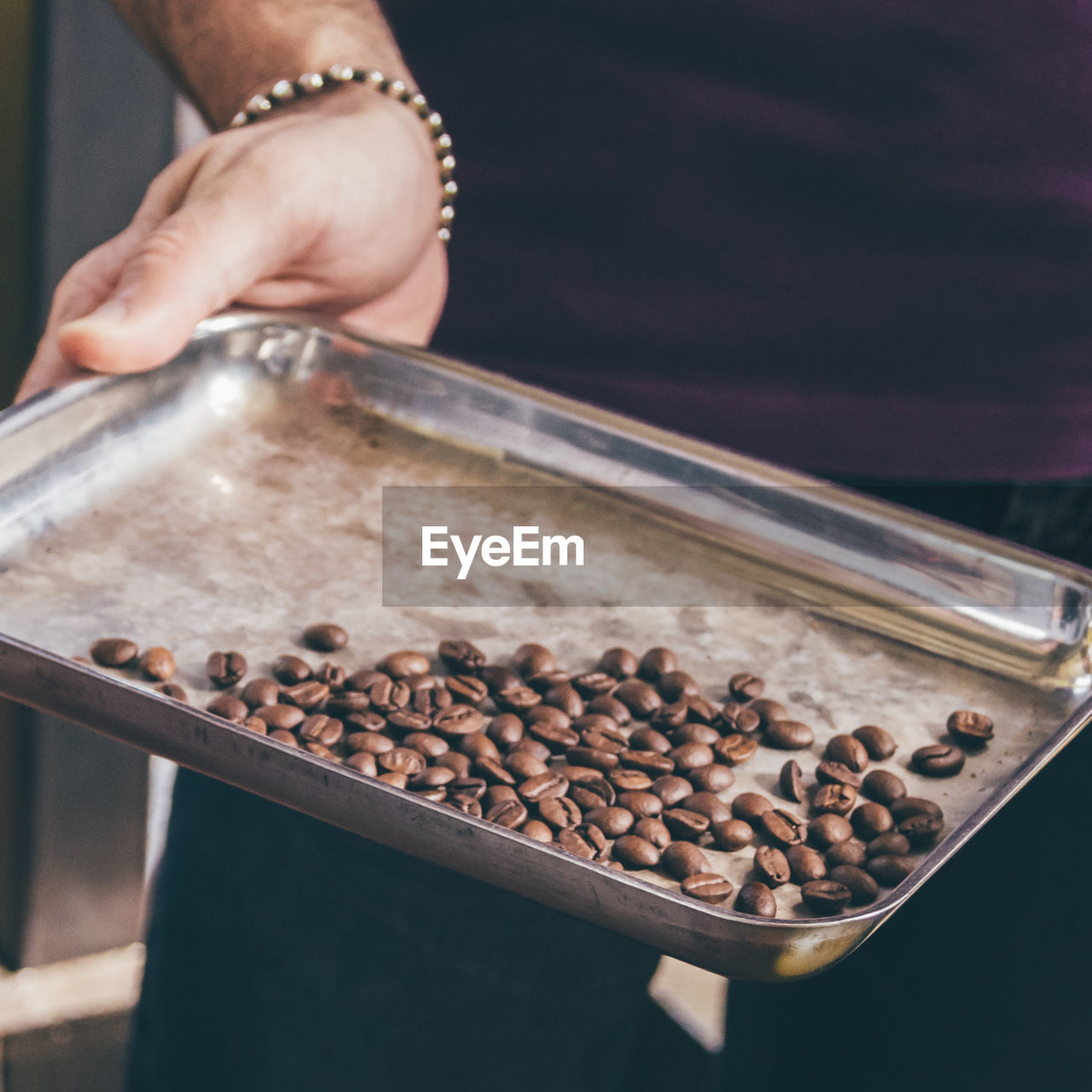 MAN HOLDING TRAY WITH COFFE BEANS