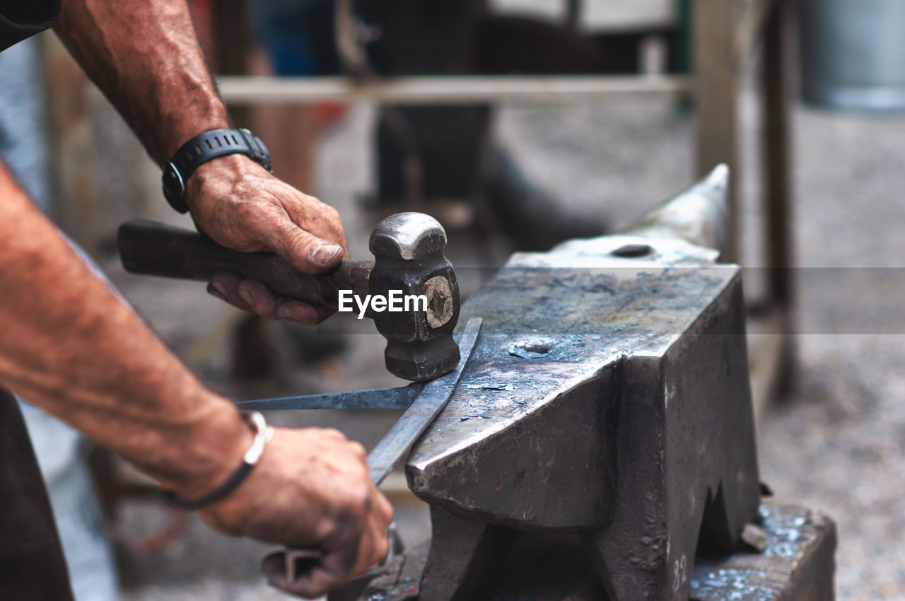 Cropped hands of blacksmith hammering metal on anvil