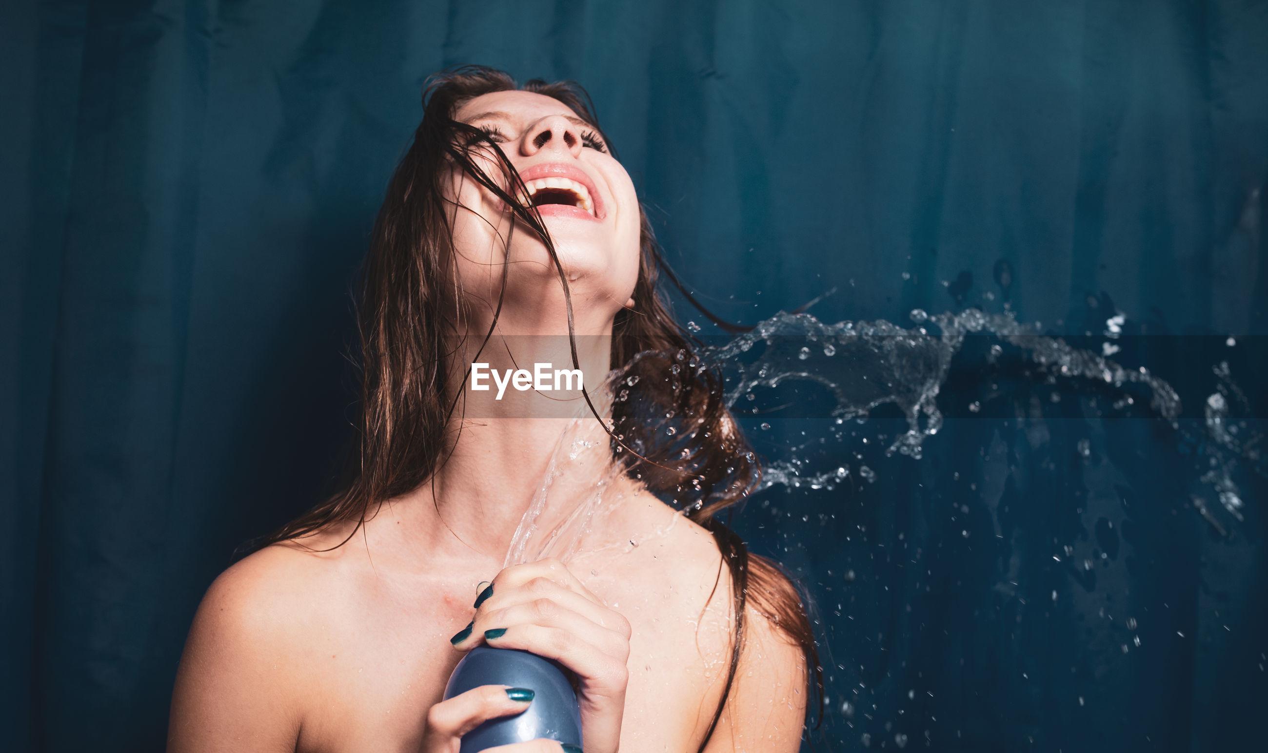 Shirtless woman splashing water against curtain