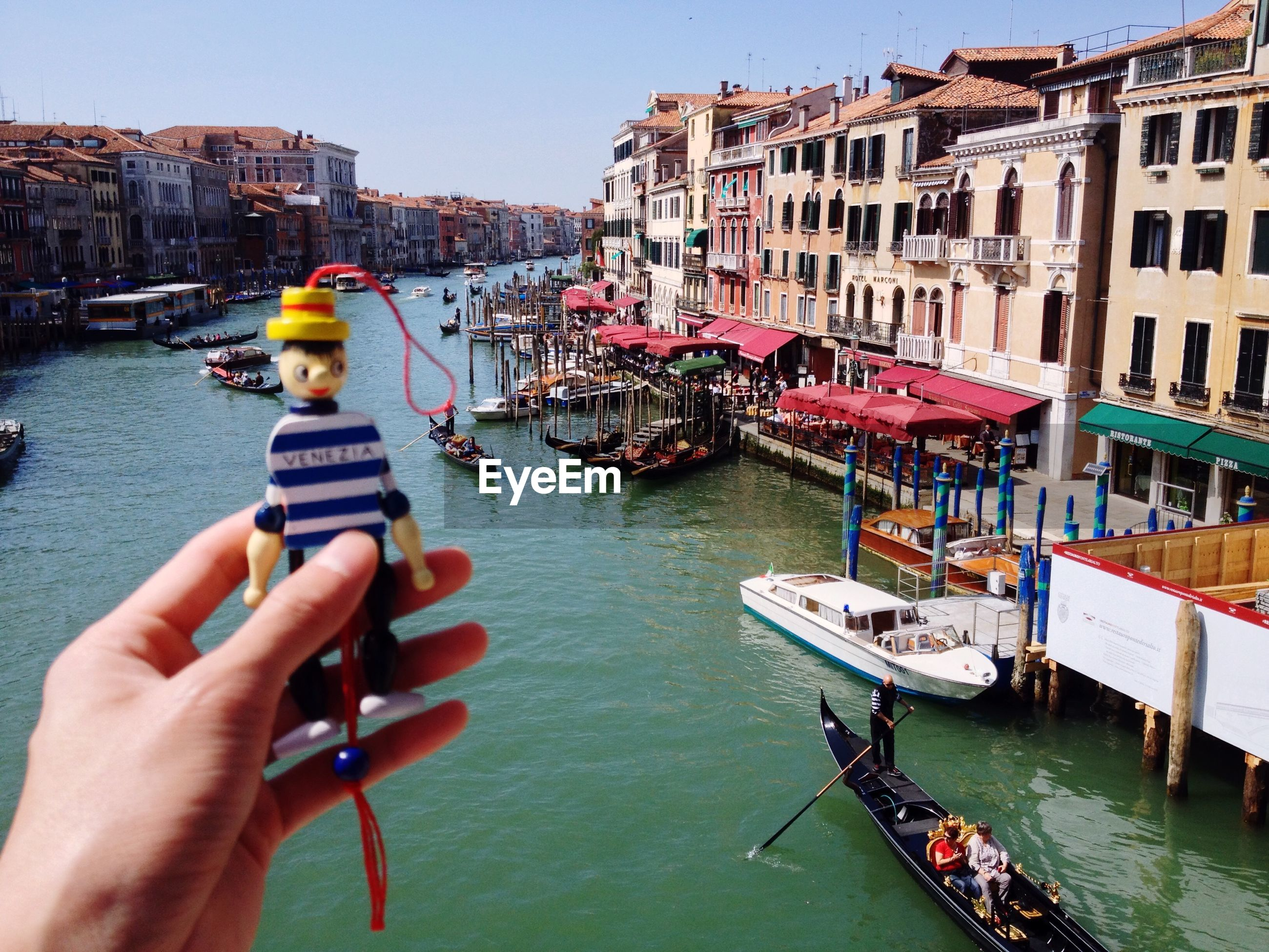 Cropped image of person holding toy by grand canal against clear sky