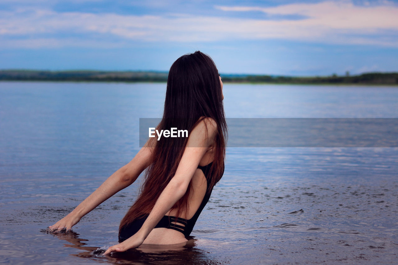 Sensuous young woman standing in sea against sky