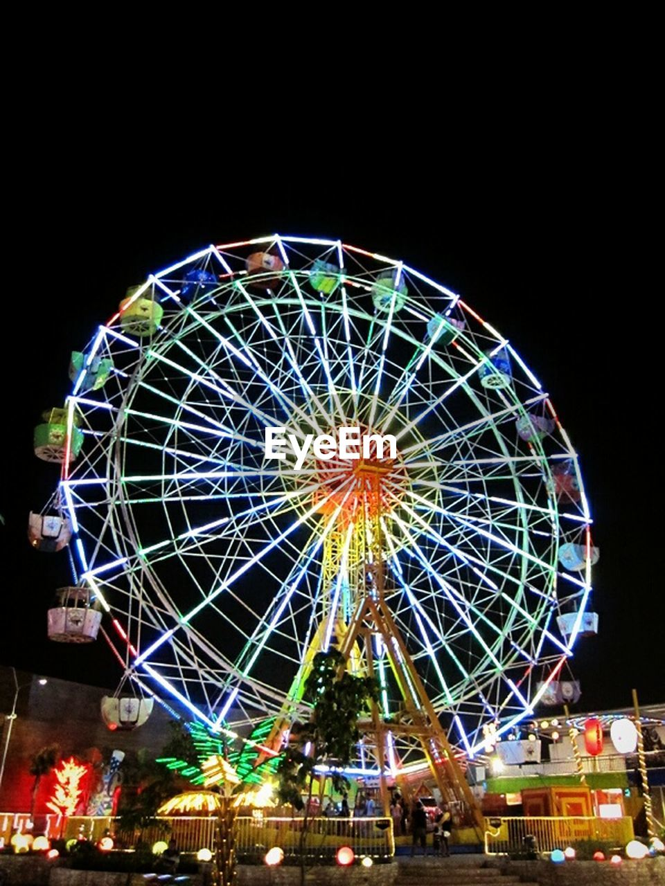 amusement park, arts culture and entertainment, ferris wheel, amusement park ride, illuminated, night, multi colored, traveling carnival, leisure activity, fun, low angle view, outdoors, sky, black background, no people, carousel