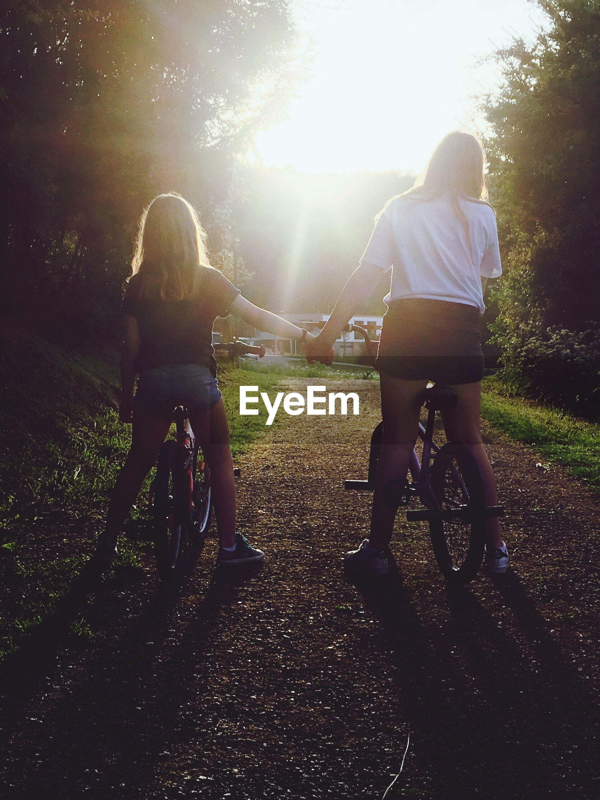 two people, bicycle, togetherness, childhood, full length, leisure activity, bonding, real people, rear view, girls, casual clothing, riding, cycling, day, happiness, outdoors, friendship, lifestyles, tree, sunlight, bmx cycling, grass, cycling helmet, nature, young adult, people