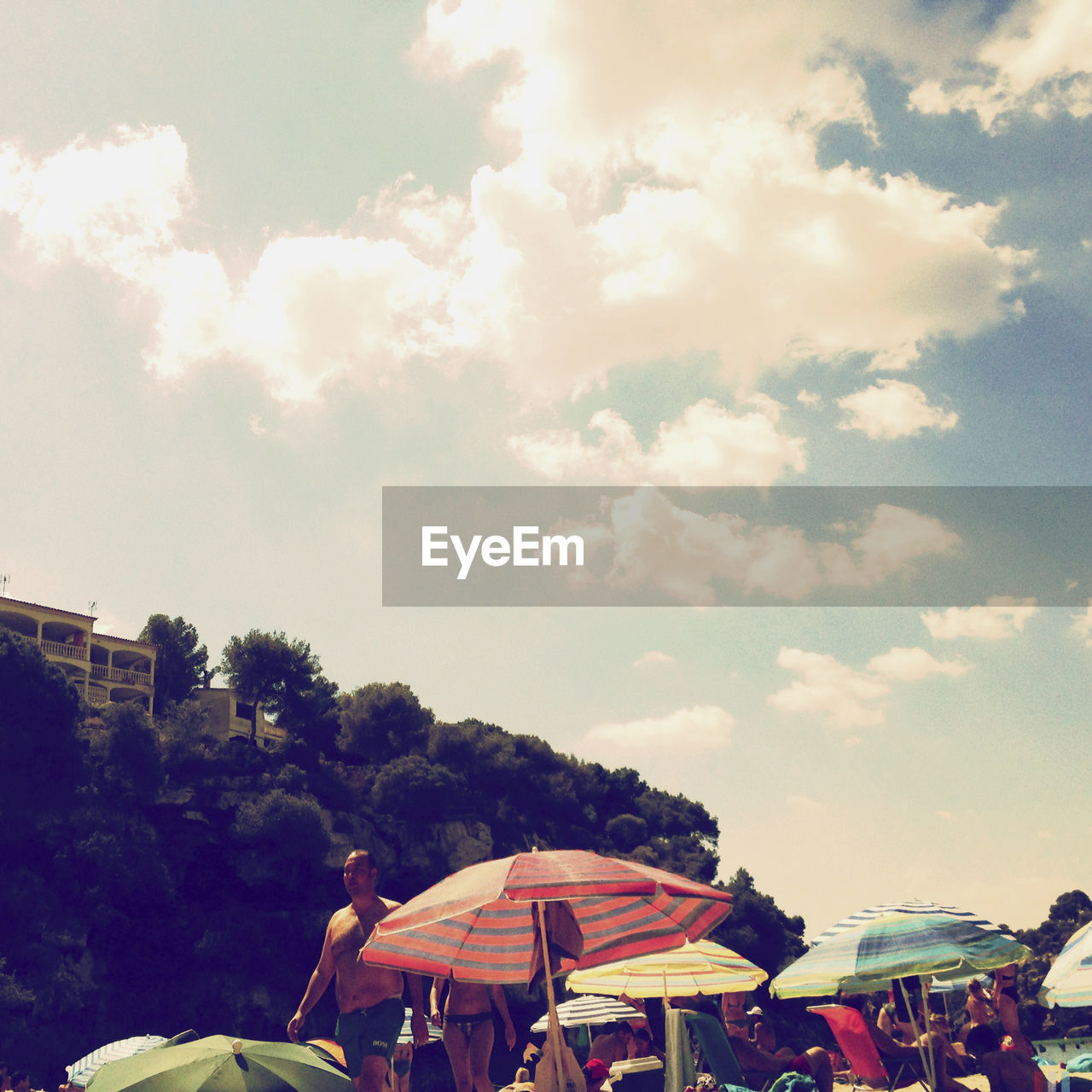 sky, cloud - sky, group of people, architecture, tree, built structure, nature, crowd, large group of people, day, leisure activity, plant, real people, arts culture and entertainment, outdoors, building exterior, amusement park, building, umbrella