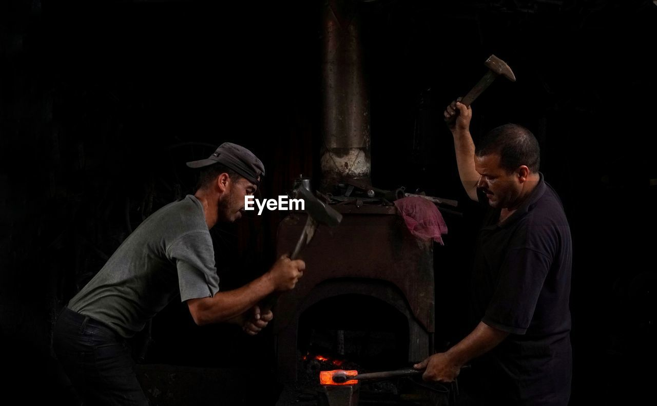 Two blacksmiths striking an iron while it's hot.