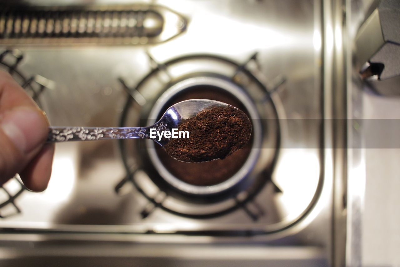 Cropped Hand Holding Spoon With Ground Coffee Over Stove
