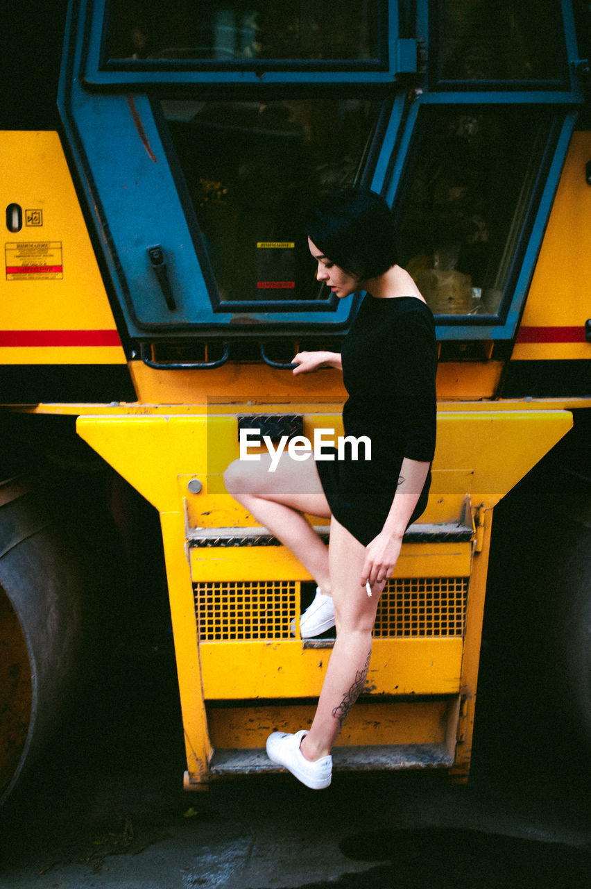 Side View Of Young Woman Standing On Vehicle Step