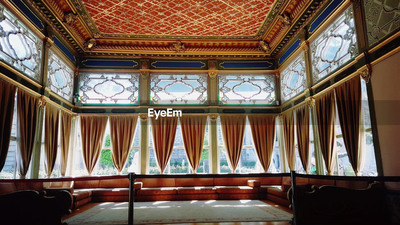 indoors, no people, architecture, window, built structure, curtain, empty, wood - material, day, building, ceiling, absence, glass - material, seat, pattern, arts culture and entertainment, travel destinations, low angle view, luxury, religion, ornate
