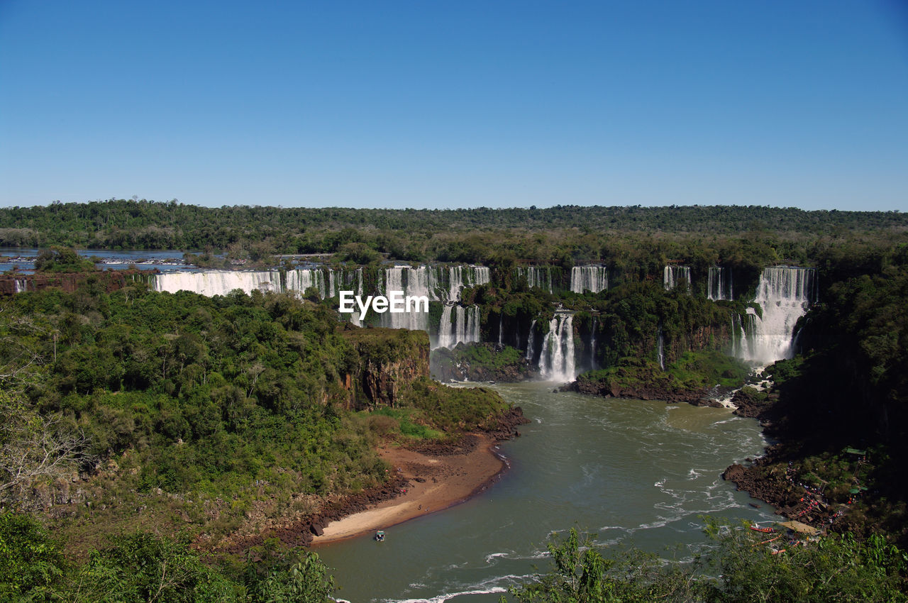 Scenic view of waterfall against clear blue sky