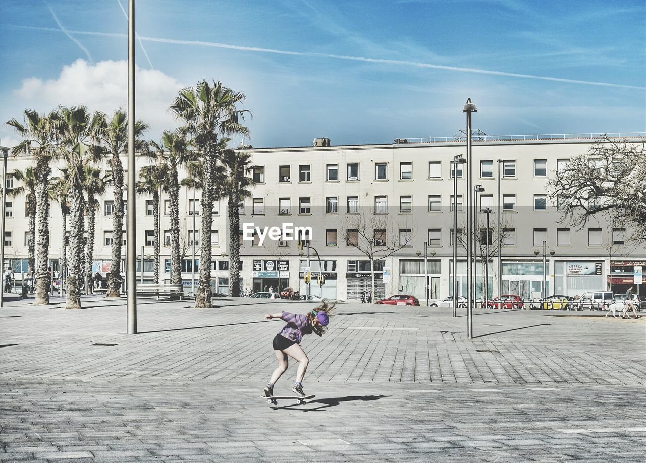 Full Length Of Woman Skateboarding At Town Square Against Sky In City