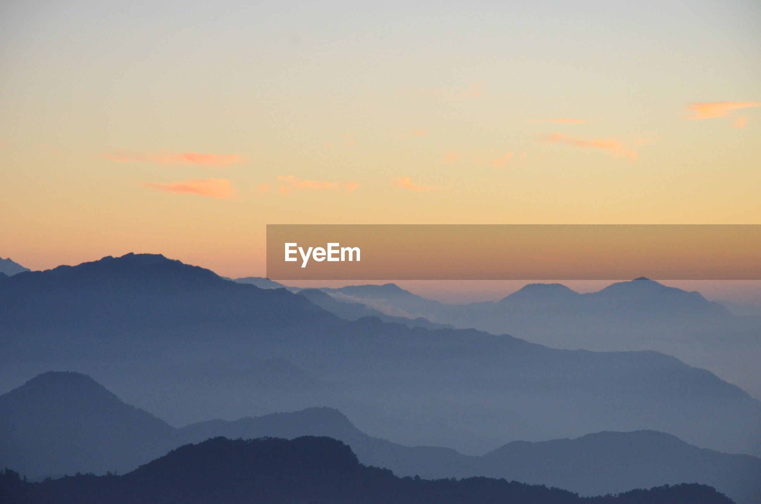 Scenic view of mountains in foggy weather during sunrise