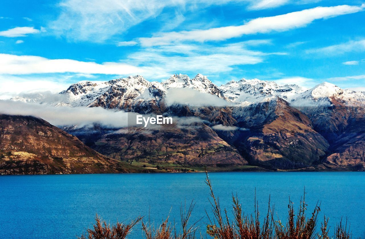 Blue Lake In Front Of Snowcapped Mountains Against Cloudy Sky During Winter