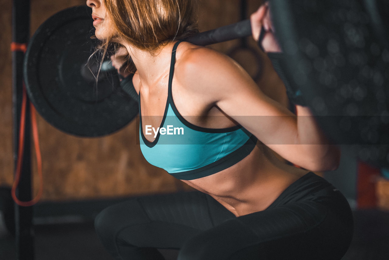 Midsection Of Young Woman Lifting Weights In Gym