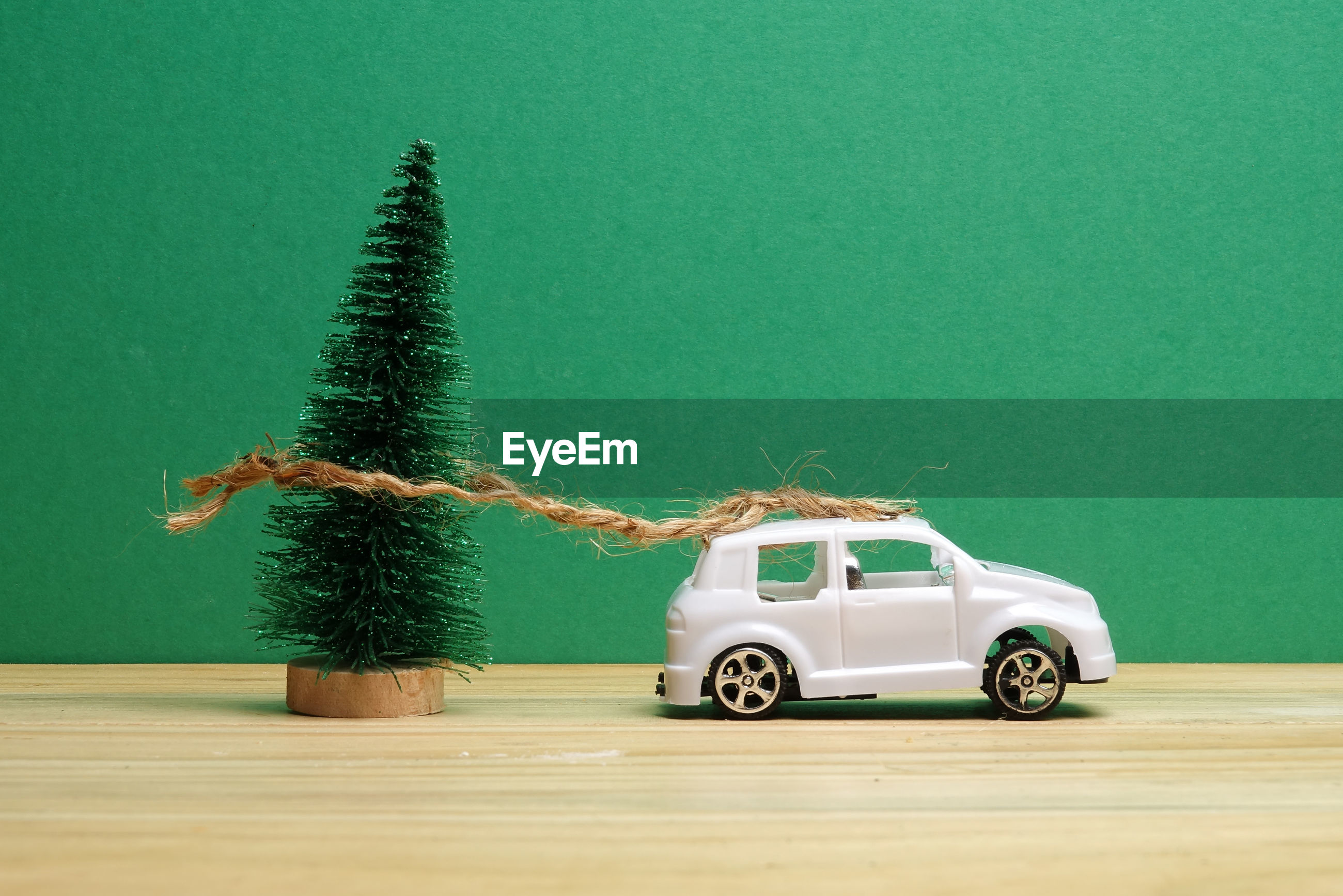 Close-up of small christmas tree tied with toy car on wooden table against green background