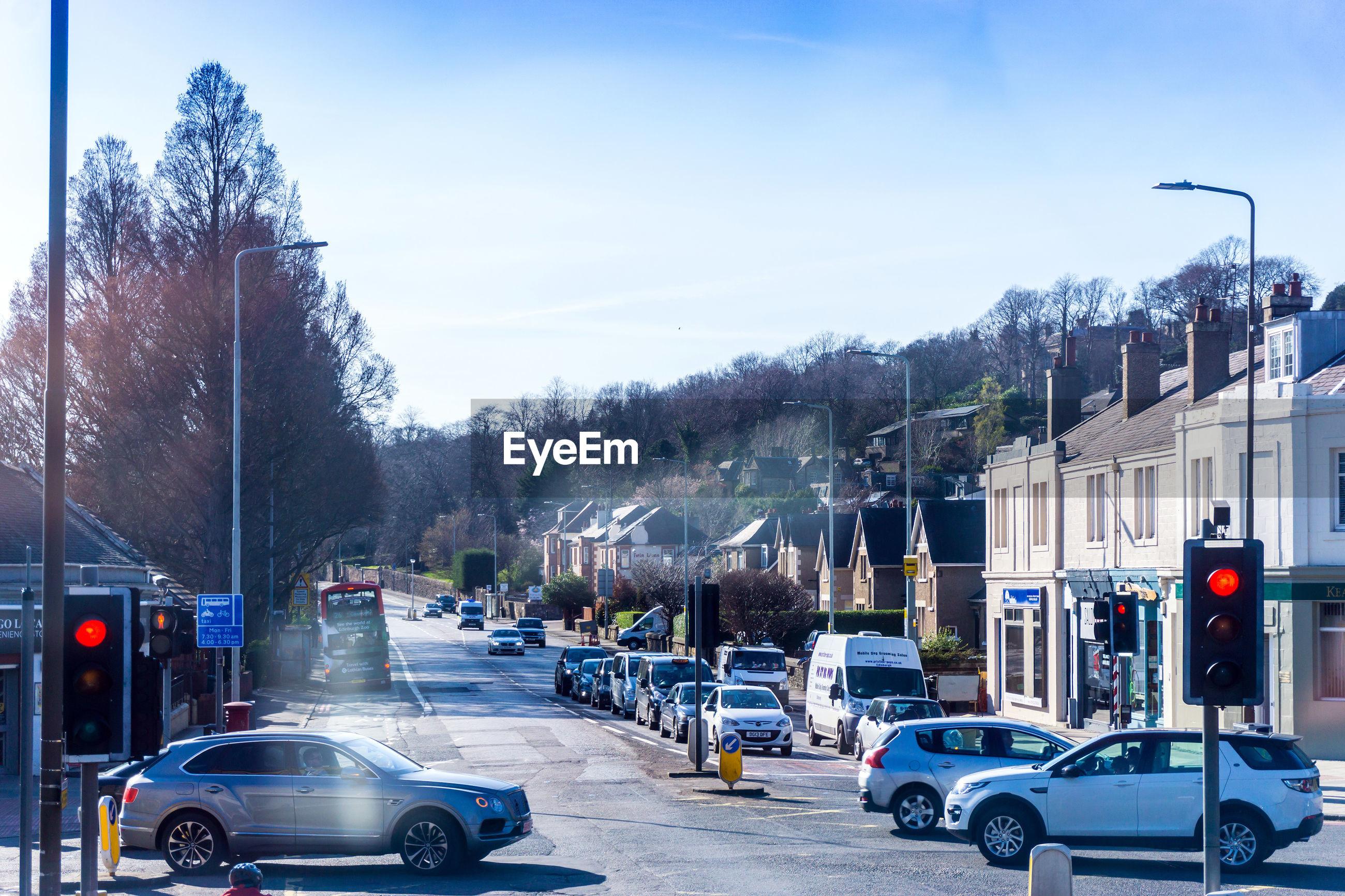 CARS ON STREET AGAINST SKY IN CITY