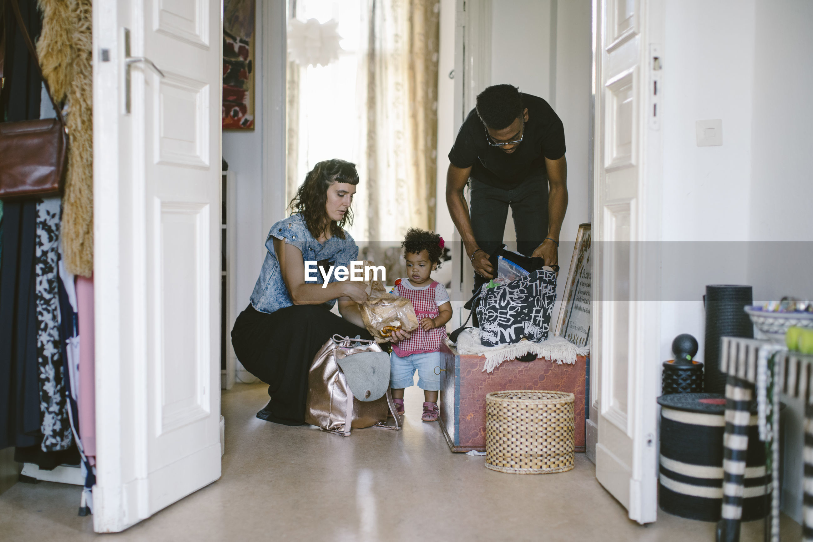 Daughter looking at mother and father packing luggage at home