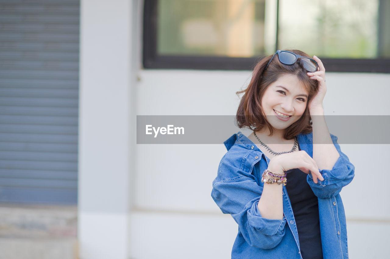 Portrait of smiling woman wearing denim jacket standing against building