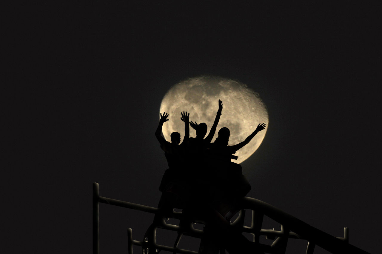 Low Angle View Of Silhouette People On Rollercoaster Against Moon At Night