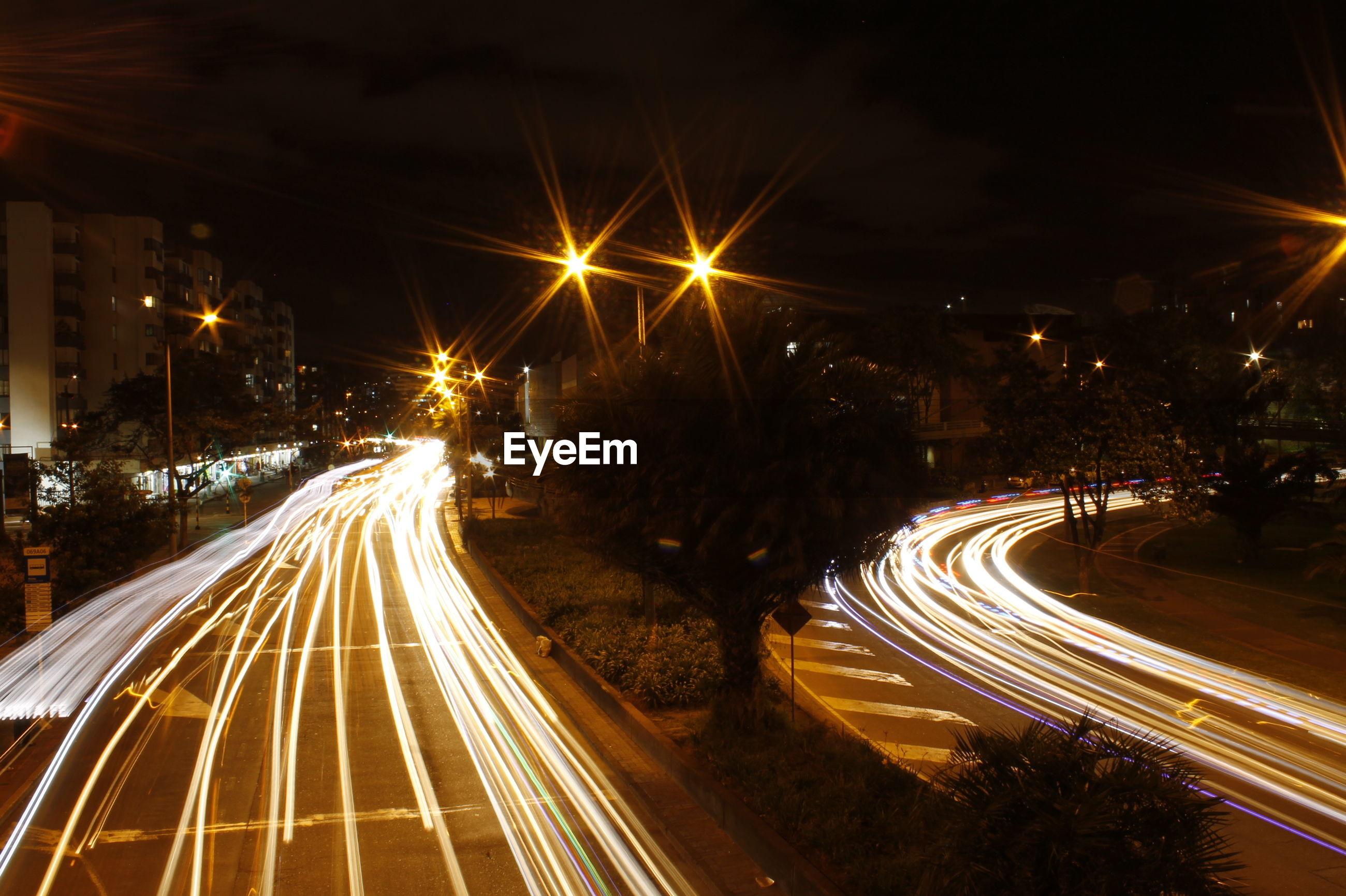 LIGHT TRAILS ON ROAD ALONG ILLUMINATED STREET LIGHTS