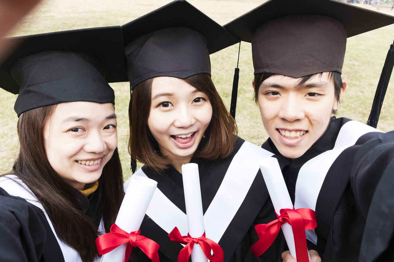 Portrait of smiling friends wearing graduation gowns with certificates at park
