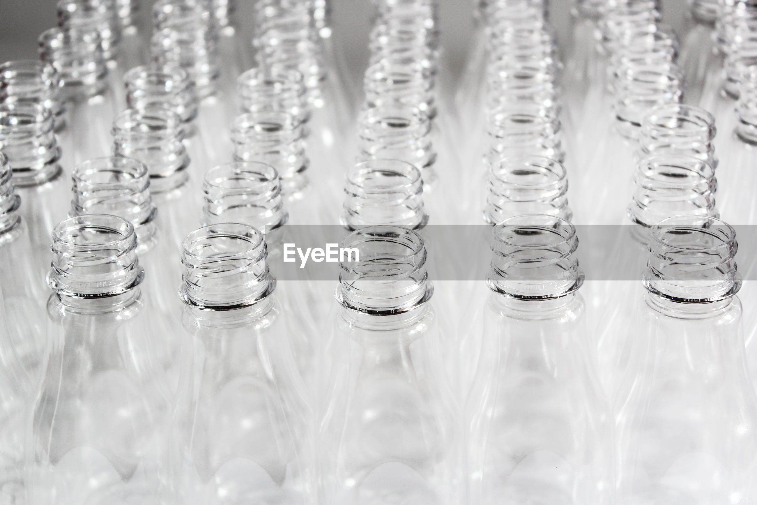 Close-up of empty glass bottles against gray background