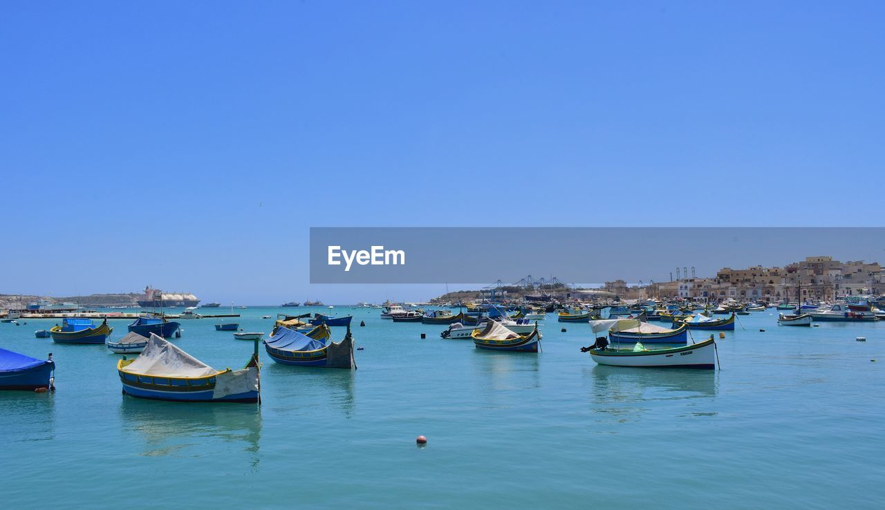 Boats Moored In Harbor Against Clear Blue Sky