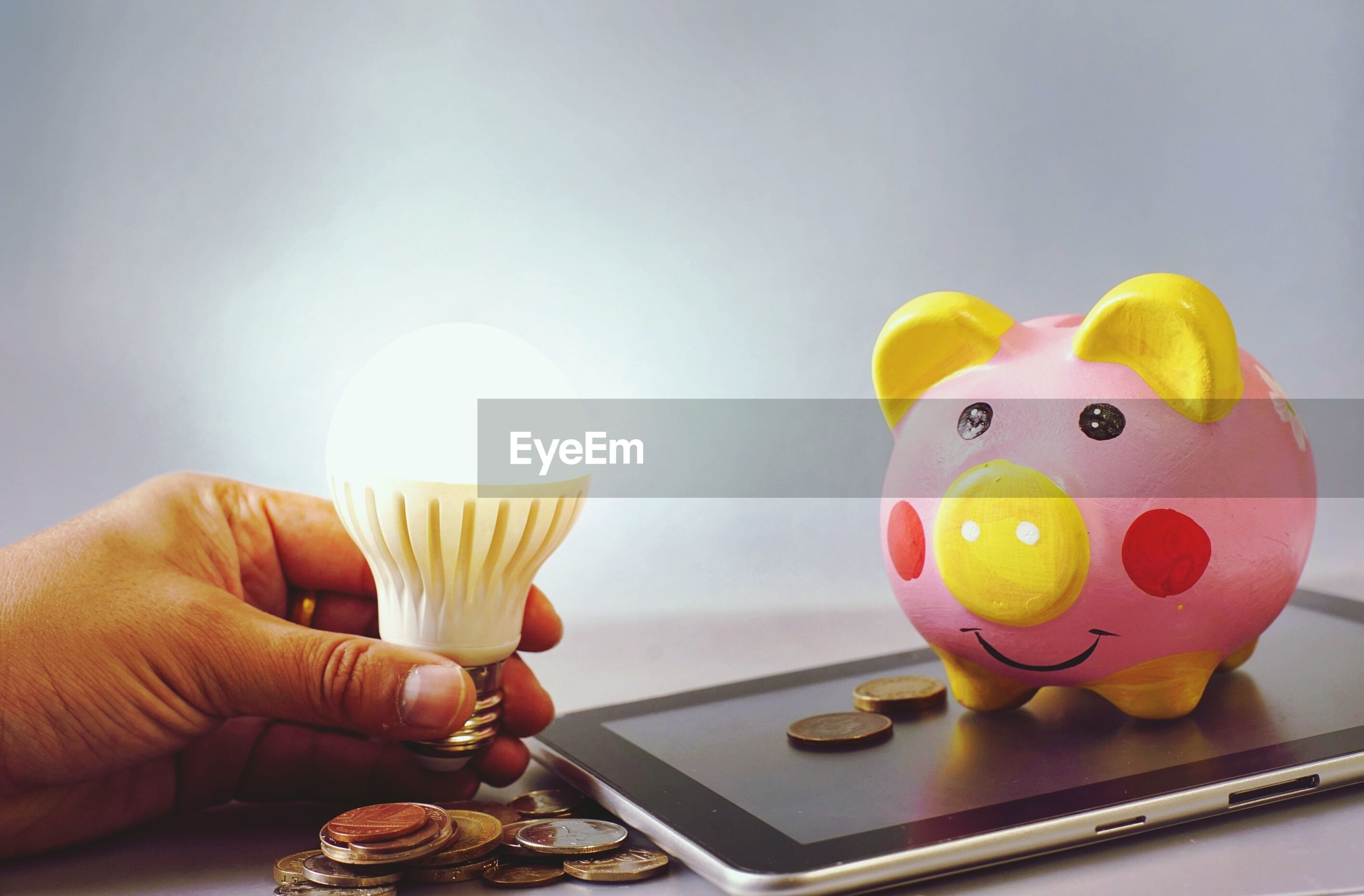 Cropped hand holding illuminated light bulb with coins and piggy bank on digital tablet