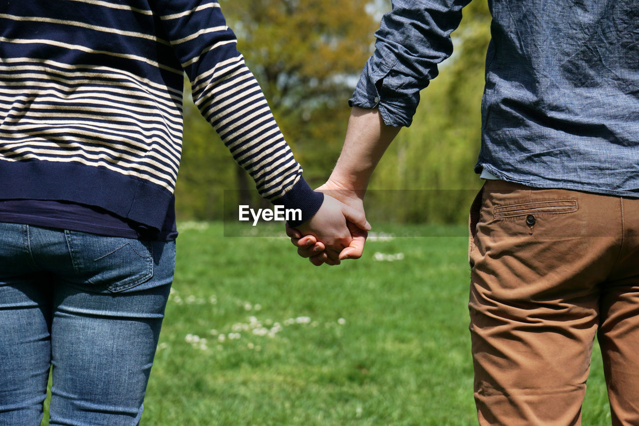 Midsection Of Couple Holding Hands At Park