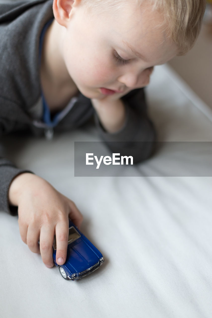 High Angle View Of Boy Playing With Toy Car On Bed