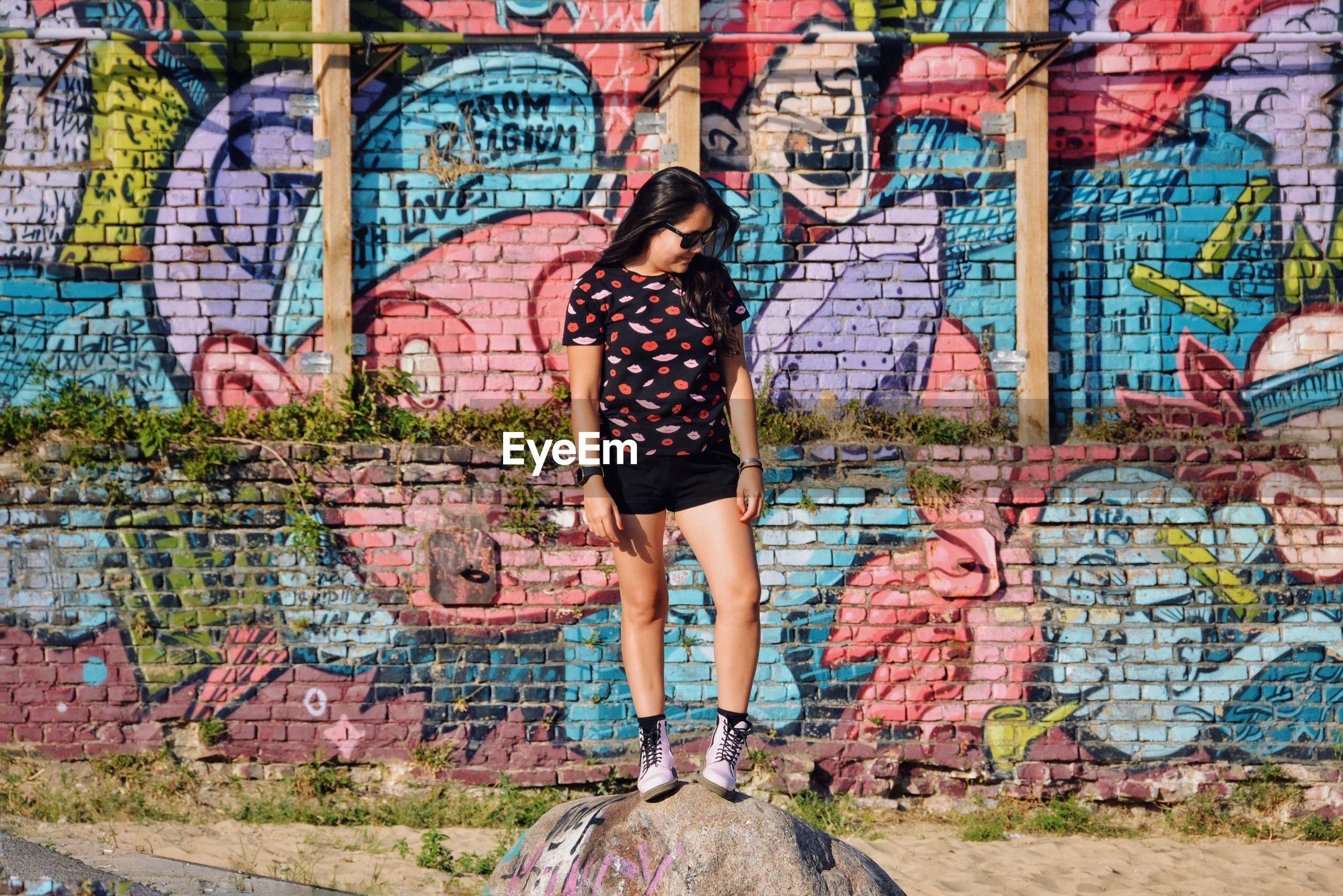 FULL FRAME SHOT OF WOMAN WITH GRAFFITI WALL