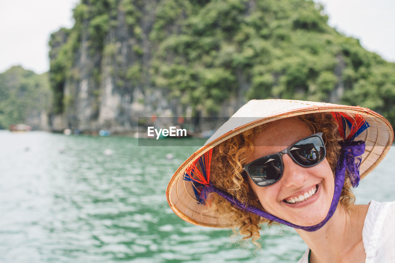 Smiling woman wearing hat and sunglasses by sea
