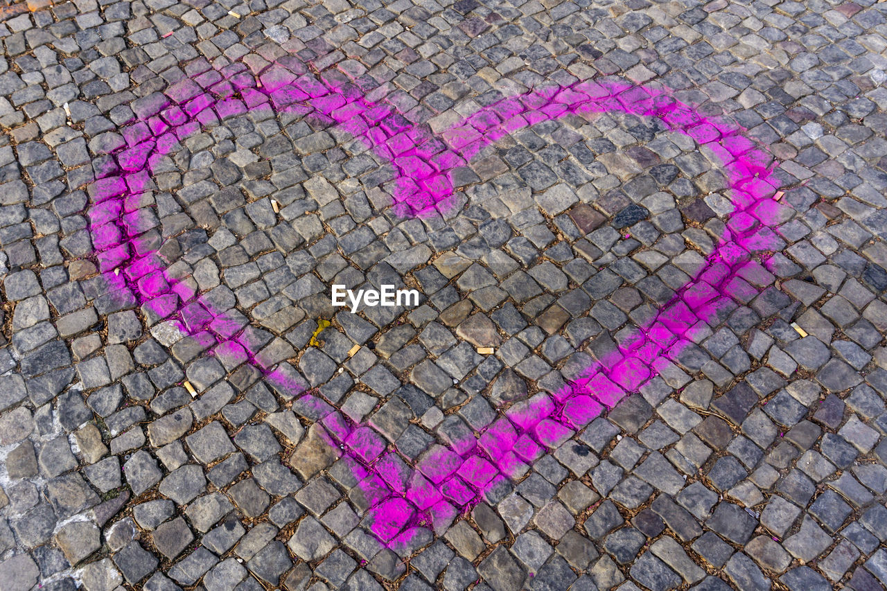 heart shape, love, positive emotion, creativity, pink color, art and craft, street, emotion, cobblestone, no people, high angle view, footpath, day, city, close-up, chalk drawing, graffiti, outdoors, craft, design, paving stone, message