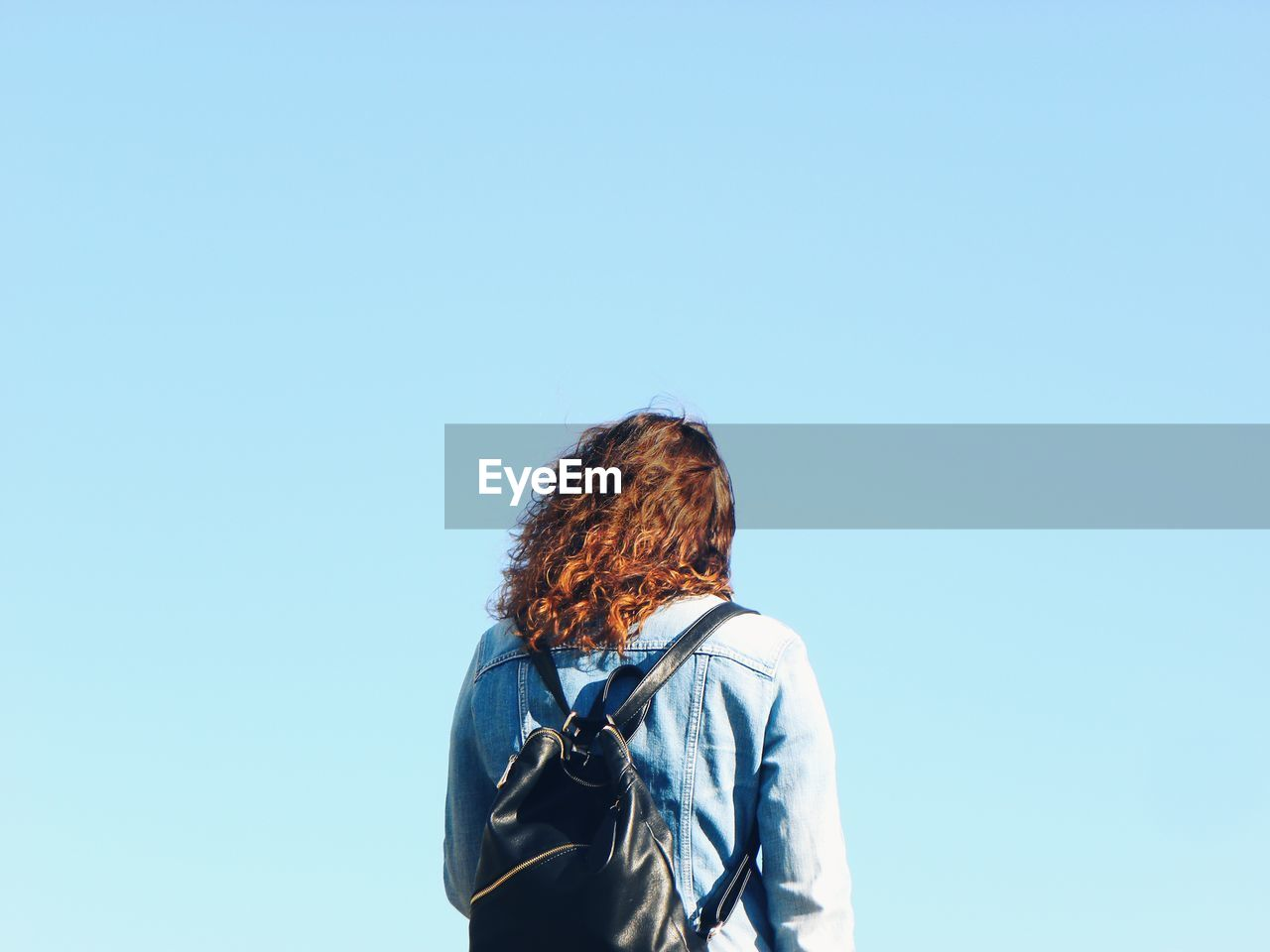 Rear view of woman standing against clear blue sky