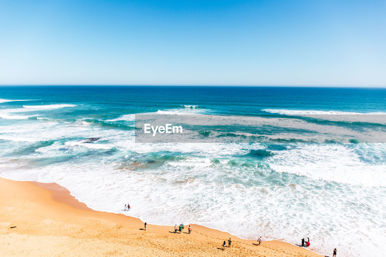 High Angle View Of People Enjoying At Beach Against Clear Sky
