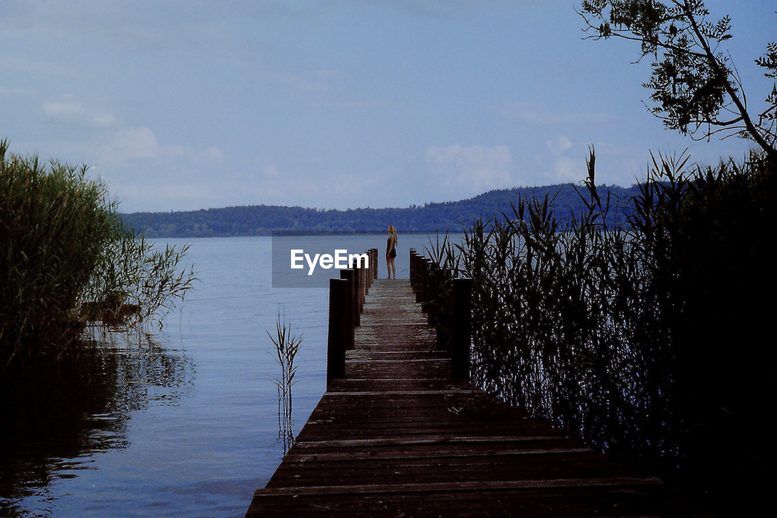 WOODEN JETTY LEADING TO PIER OVER LAKE AGAINST SKY