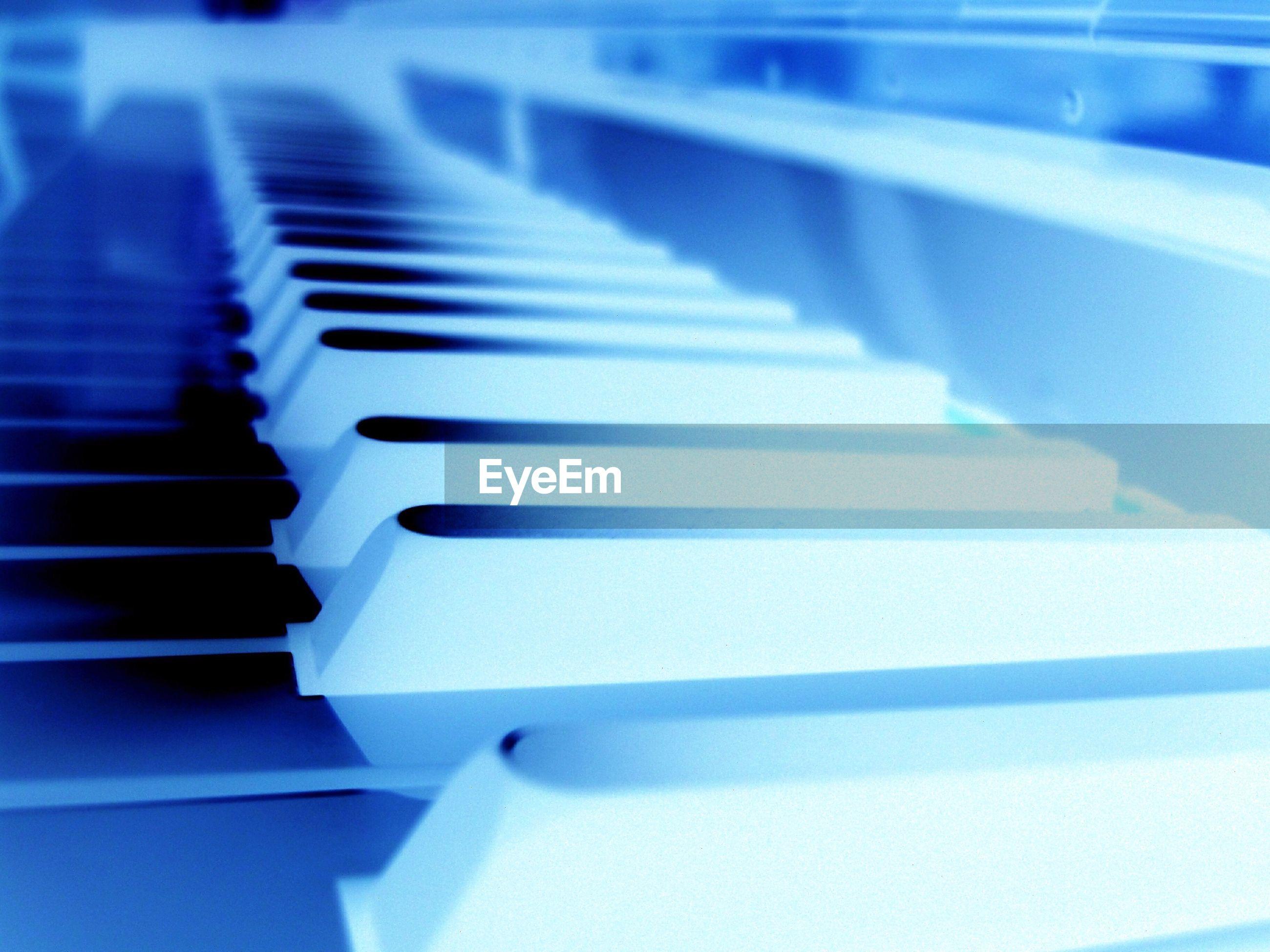 HIGH ANGLE VIEW OF PIANO KEYS AT STAIRCASE