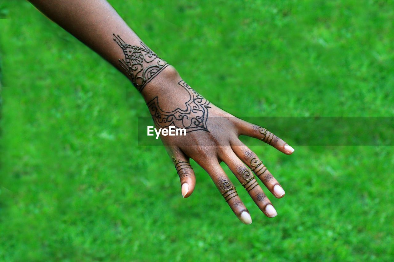 Close-up of cropped hand with henna tattoo over grassy field