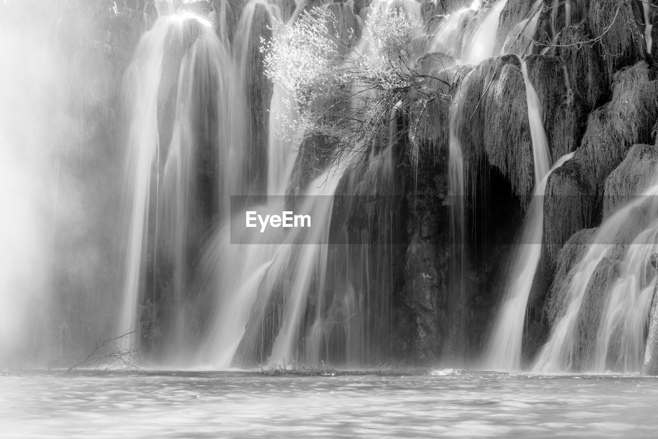 SCENIC VIEW OF WATERFALL AGAINST BLURRED BACKGROUND