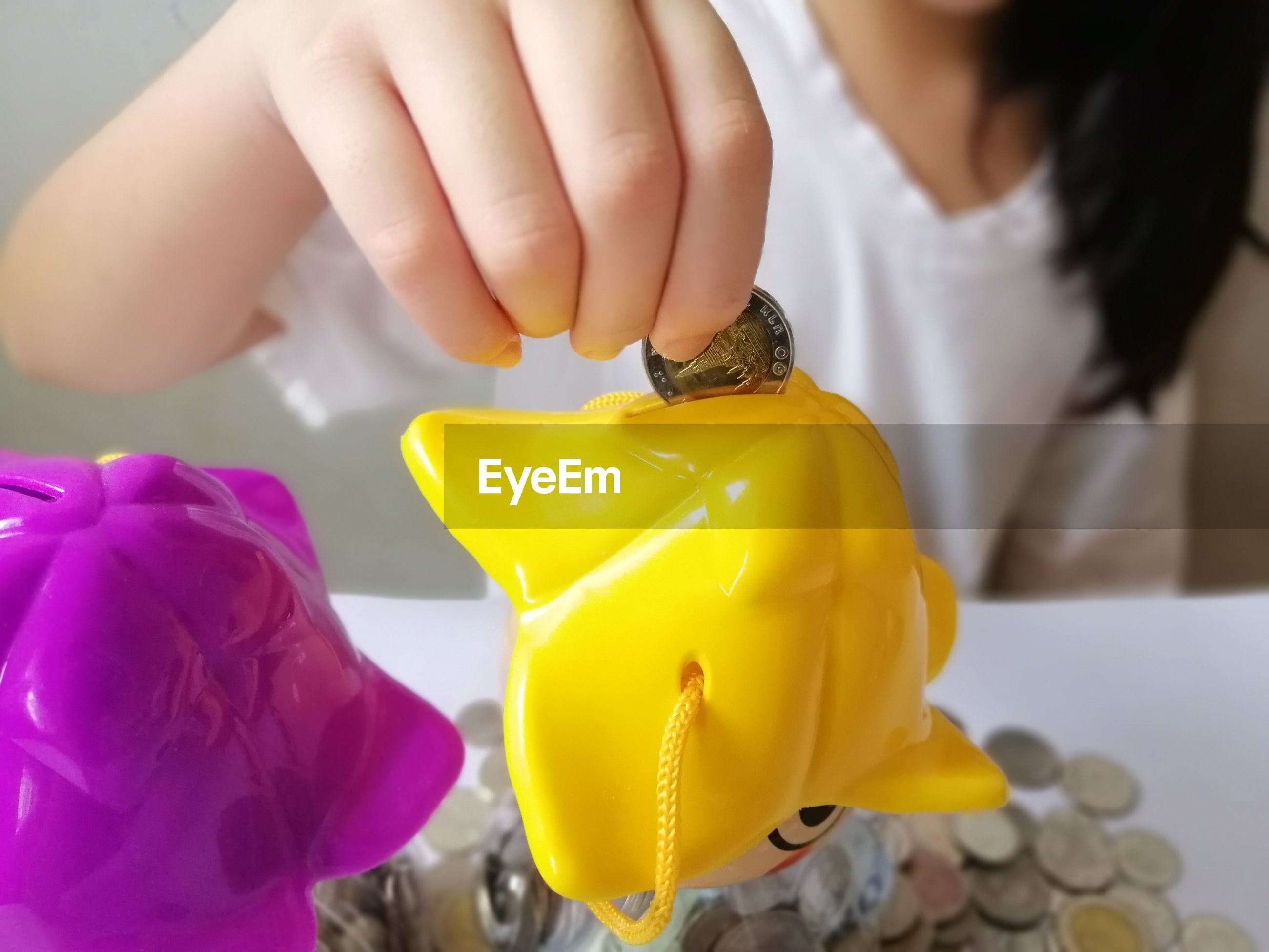 Midsection of woman inserting coin in piggy bank